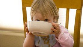 Little girl in a chair sipping from a bowl