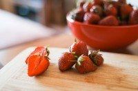 Strawberries on a cutting board and in a bowl