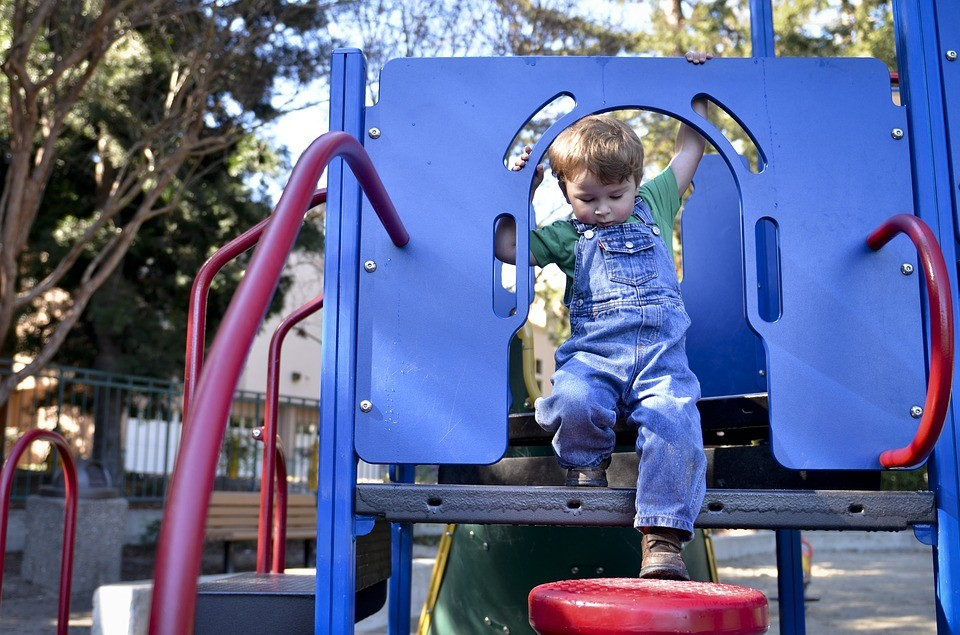 Little child stepping down from play structure