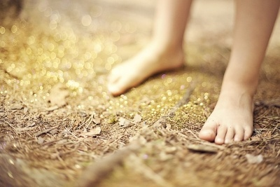 Child standing barefoot on ground