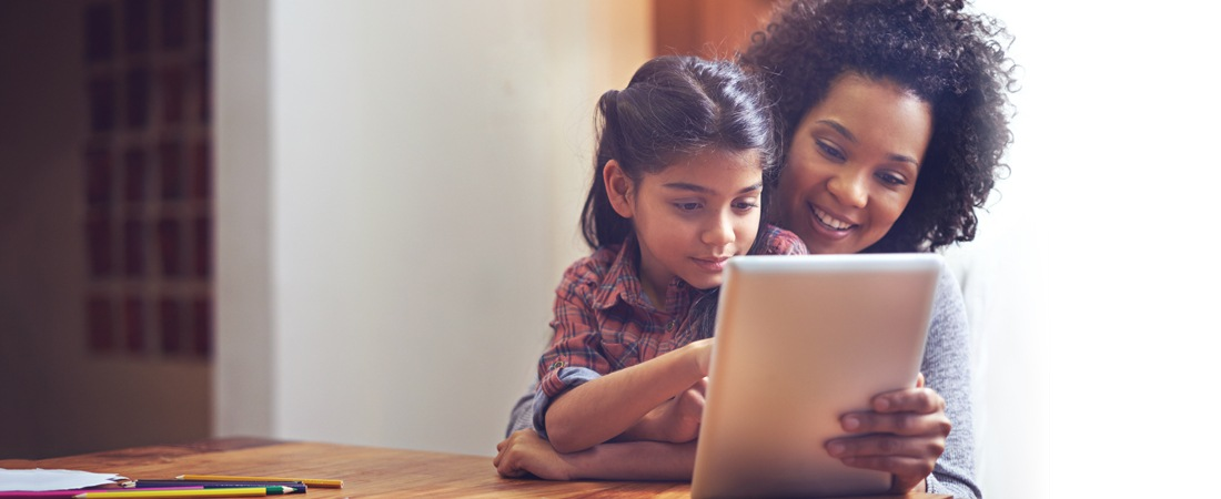 Mother and daughter playing together on tablet device