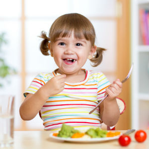 Young girl eating her vegetables