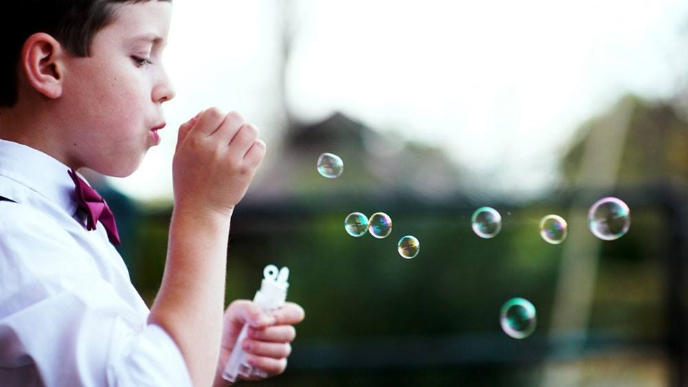 Little boy in a red bow-tie blowing bubbles