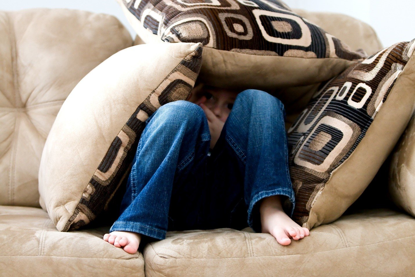 Young child hiding behind pillows on a couch