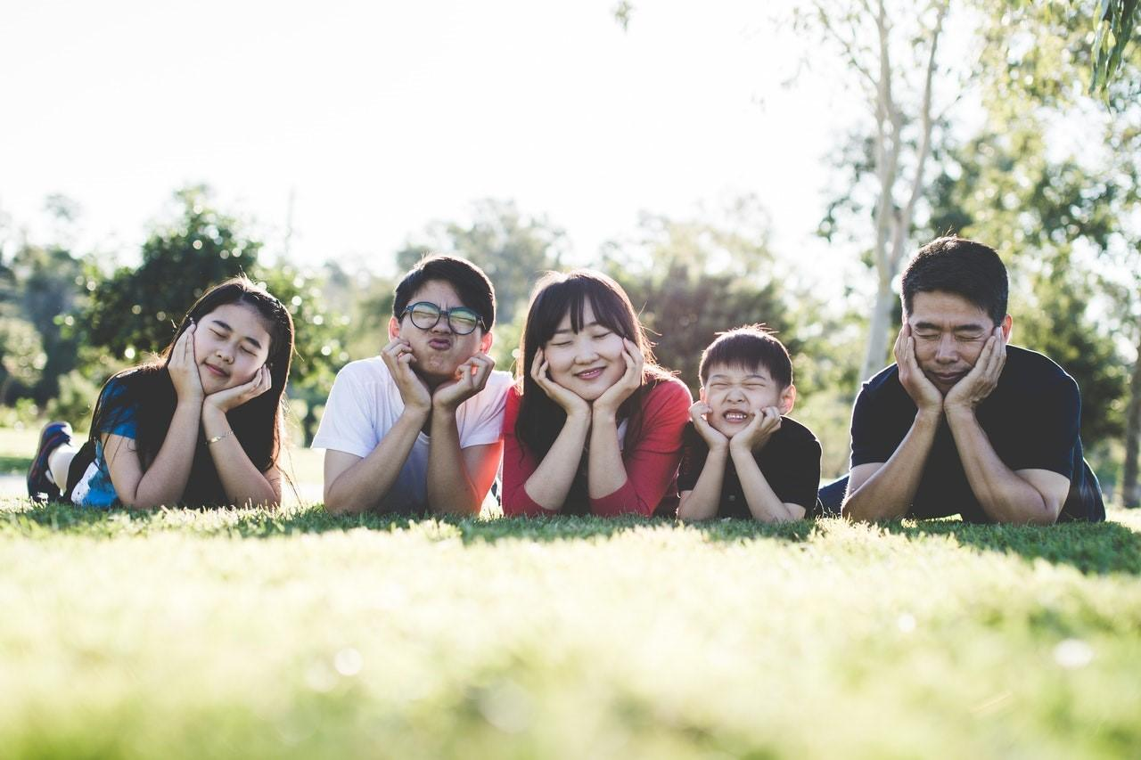 Family lying on their stomachs in the grass and smiling
