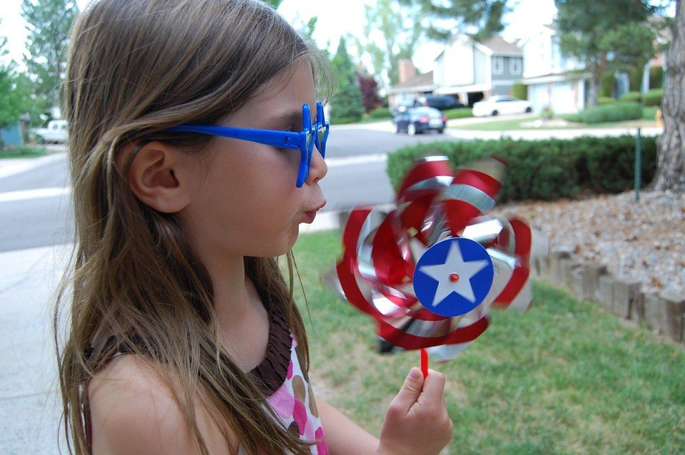 Little girl blowing on red, white, and blue pinwheel