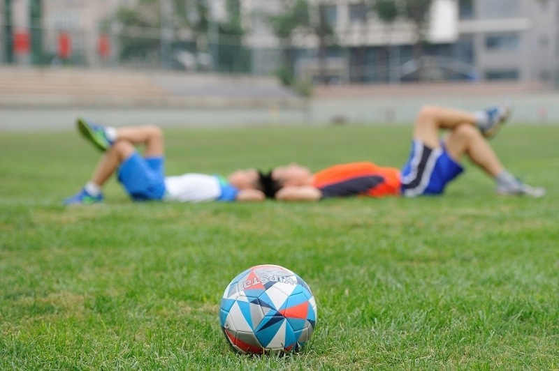 Two young boys resting from playing soccer
