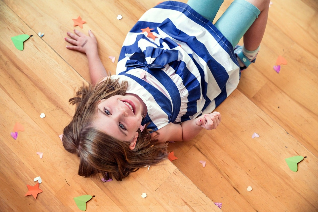 girl smiling while laying on wood floor with arts and crafts